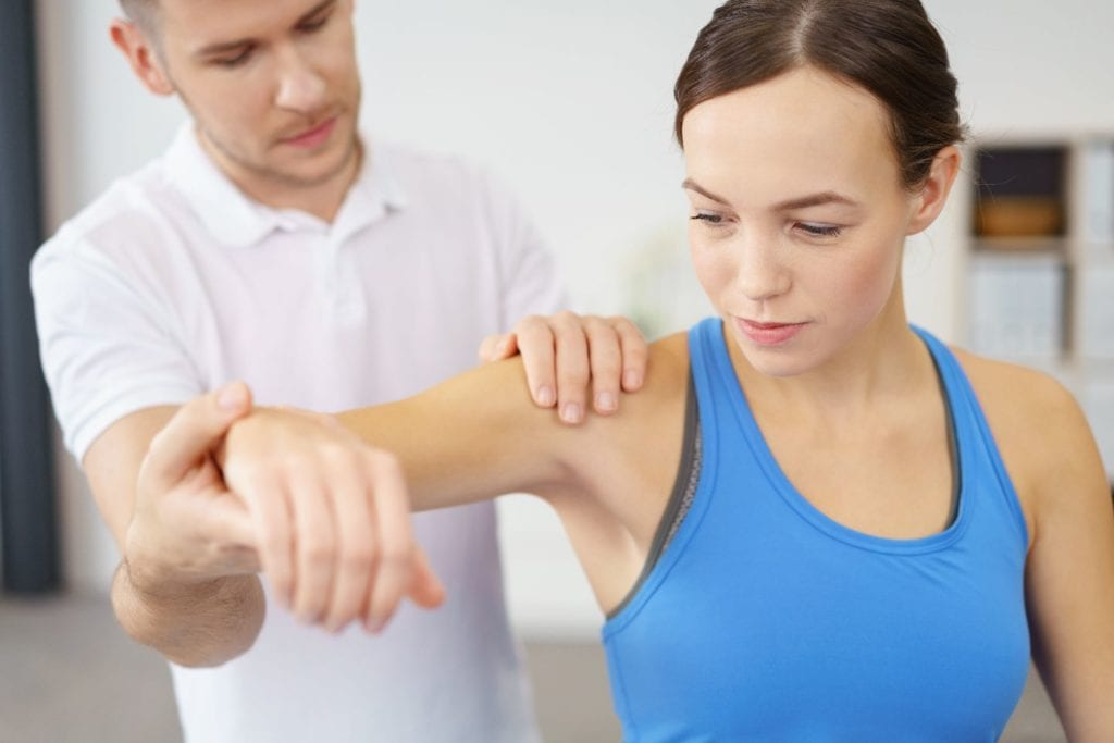 Osteopath examining patients shoulder in the seated position