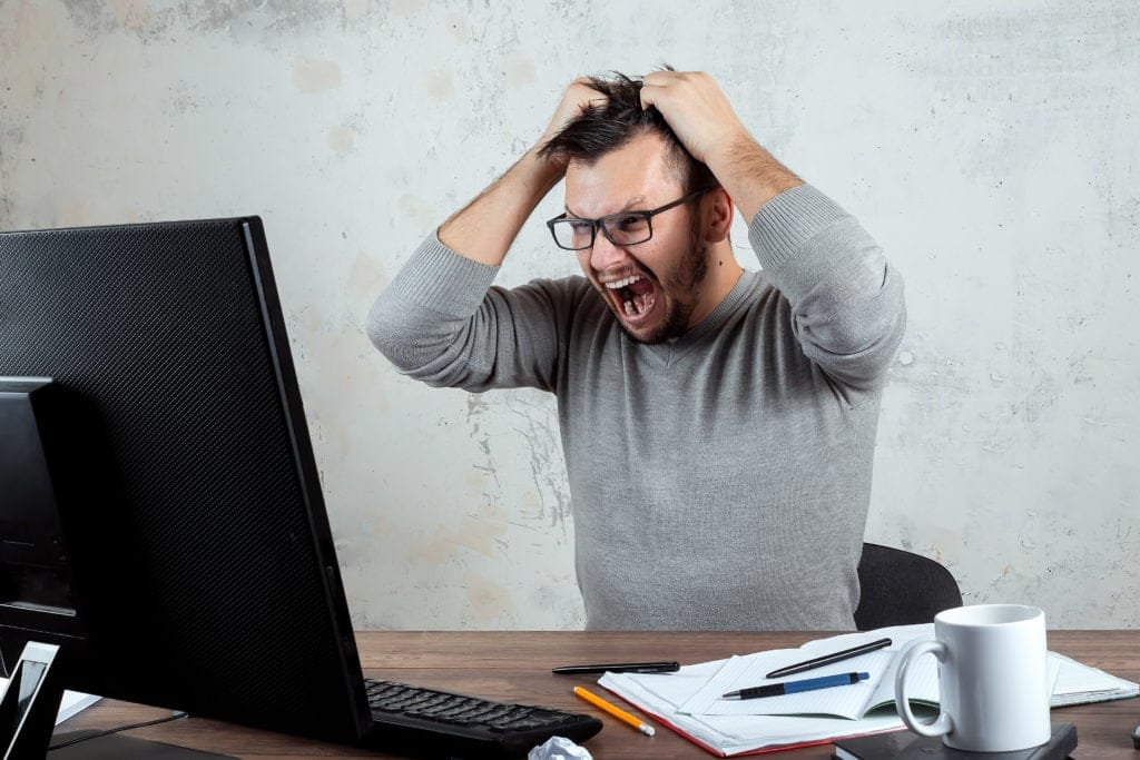 A man is stressed out at his desk
