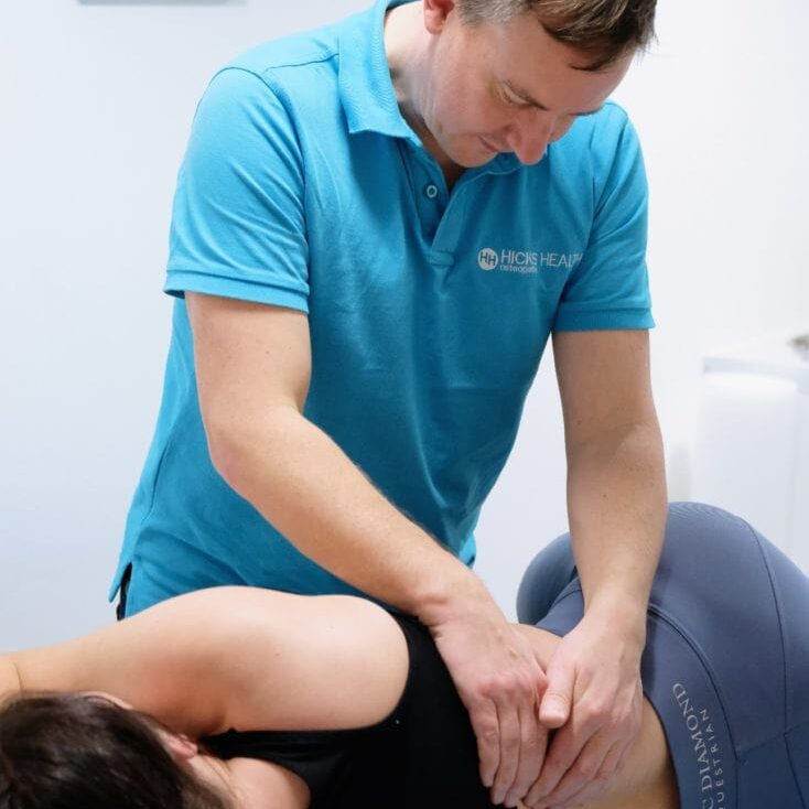 Osteopath Oliver Hicks Performing osteopathy and sports massage 0n a patient with low back pain